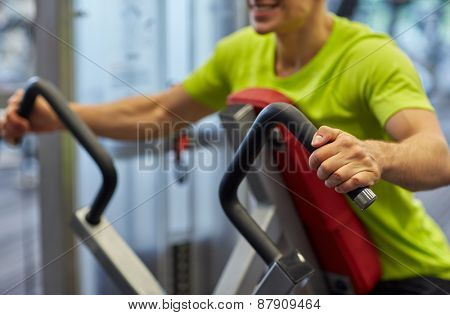 sport, fitness, lifestyle and people concept - close up of smiling man exercising on gym machine