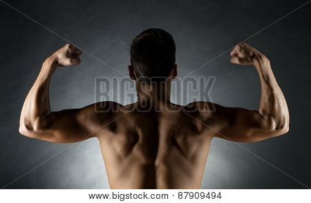 sport, bodybuilding, strength and people concept - young man showing biceps over gray background from back