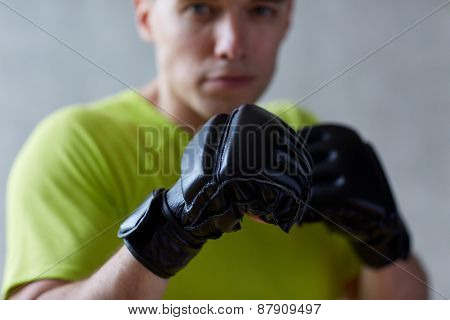sport, competition, strength and people concept - young man in fighting or boxing position over concrete wall background