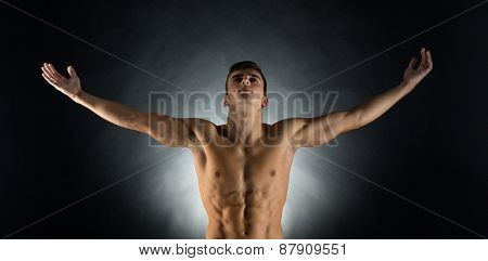 sport, bodybuilding, strength and people concept - young man standing with raised hands over black background