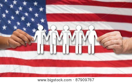 community, unity, international, social equality and teamwork concept - close up of multiracial couple hands holding paper chain people over american flag background