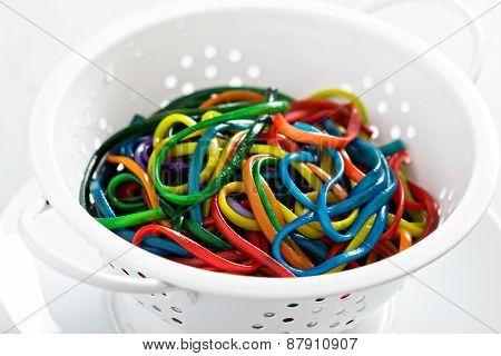 Rainbow colored spaghetti in a colander