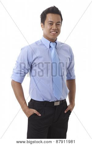 Portrait of confident young Asian businessman in shirt and tie, standing arms crossed, smiling at camera.