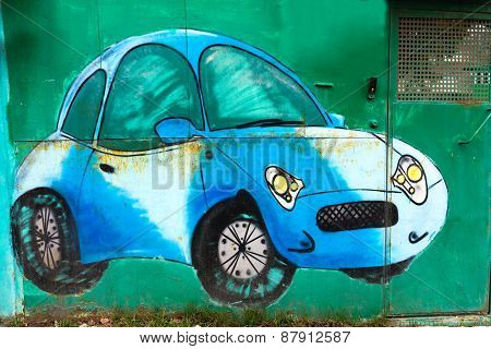 Moscow, April 14: Graffiti On The Wall, Painted Blue Car On The Green Wall April 14, 2015 In Moscow.