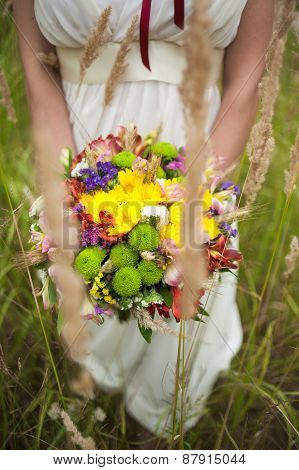 Young Bride With Bouquet Of Flowers In Her Hands