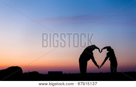 Woman And Man Hand Silhouette Over Sky At Sunset Background