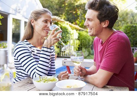 Couple Enjoying Outdoor Drinks In Garden