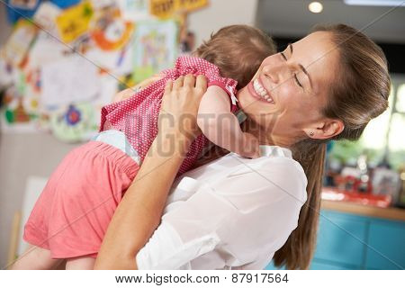 Mother Returning From Work Hugging Young Daughter