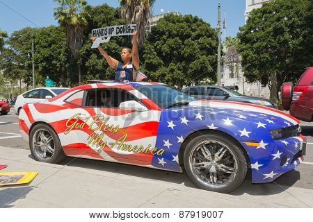 Woman Holding Sign Next To A Car Painted In American Flag Colors