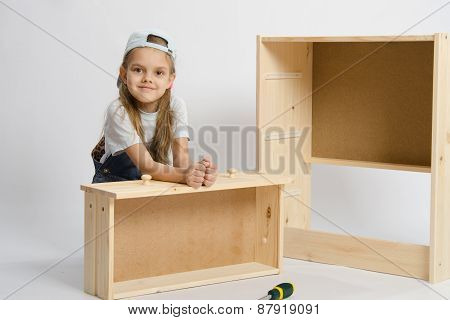 The Child Sits With A Skeleton Chest And Box