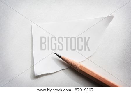 Torn corner piece of memo paper on white desk, with by-the-window type lighting.