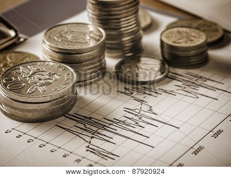 Coins and graph in sepia tone