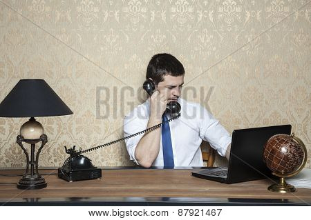 Businessman Working On Laptop And Talking On The Phone