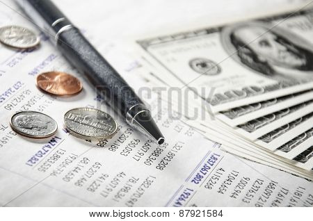 Pen, coins, and cash on paper