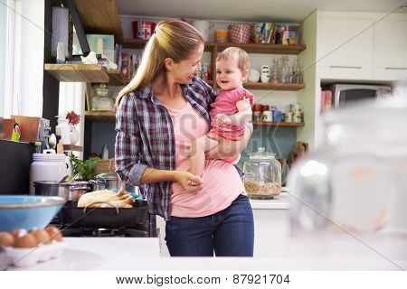 Mother Cooking Meal Whilst Holding Daughter In Kitchen