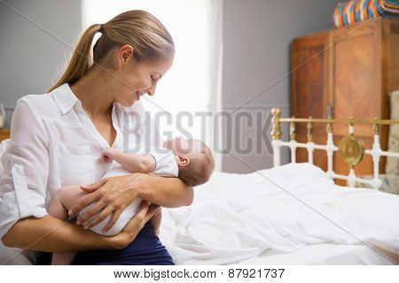 Mother Dressed For Work Holding Baby In Bedroom