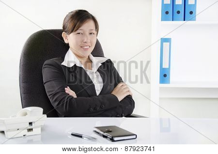 Businesswoman sitting with arms crossed