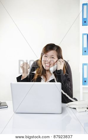 Businesswoman cheering on the phone