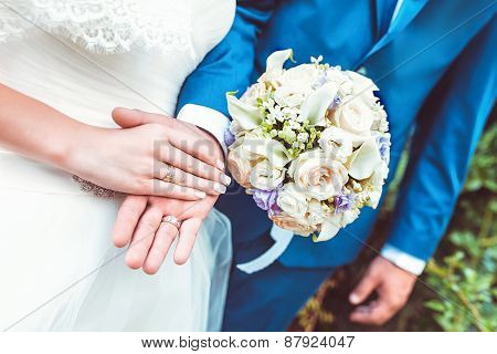 Newlyweds Couple Holding Hands With Rings And Wedding Bouquet