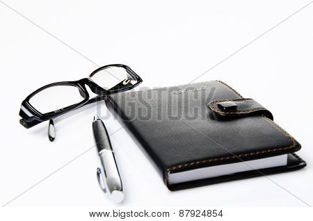 Black glasses, notebook and ballpoint pen