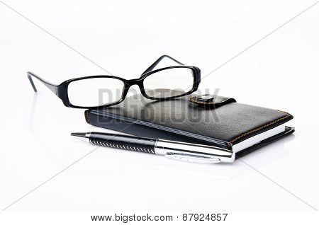 Notebook, glasses and black ballpoint pen