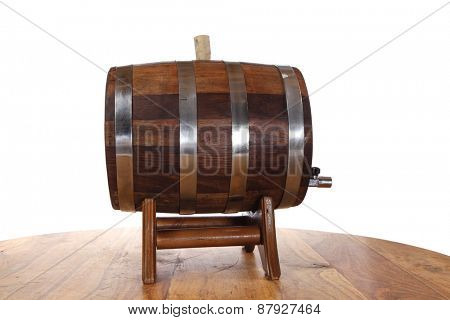 hand made wooden barrel full whiskey with crane over wooden table isolated over white background