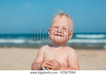 Adorable Girl At Beach Applying Sunblock Cream