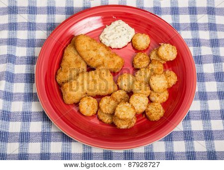 Fried Fish Fillets And Potato Puffs On Red Plate