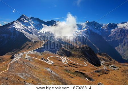 Famous picturesque views of the road in Austrian Alps - Grossglocknershtrasse. The highest mountain peaks covered with fresh snow. Ideal highway winds high in the mountains