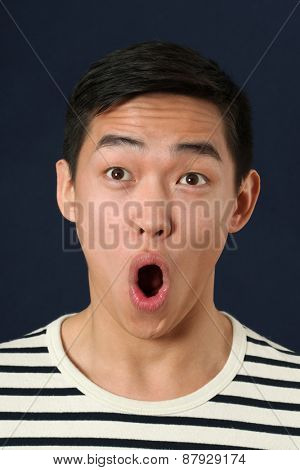 Astonished young Asian man looking upward