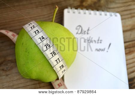 Diet concept with green apple, a notebook and a measuring tape on wooden table