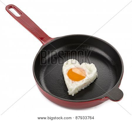 Heart shaped egg on cast iron cookware isolated on white background.