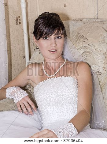 Young brunette bride posing for the camera indoors