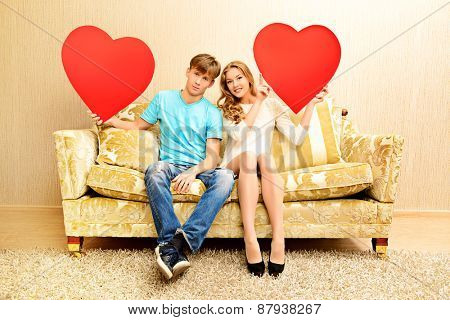 Romantic young couple sitting relaxed on a sofa in the cozy living room of their home. They hold big red hearts. Valentine day.