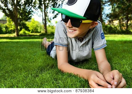 Cool boy lying on a grass at a park and smiles. Summer day. Holiday.