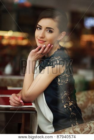 Beautiful Young Brunette Woman Sitting Dreamy Near A Window In A Restaurant, View Through The Window