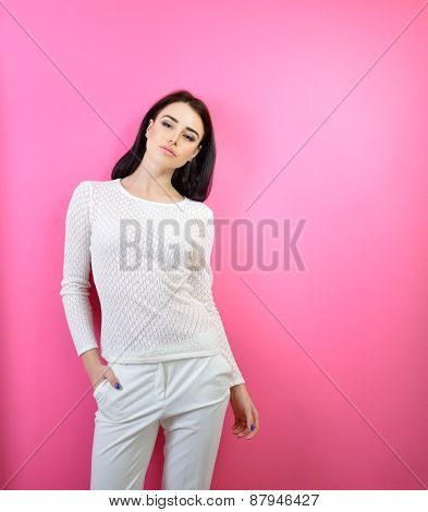 Portrait of young fashion girl over pink background
