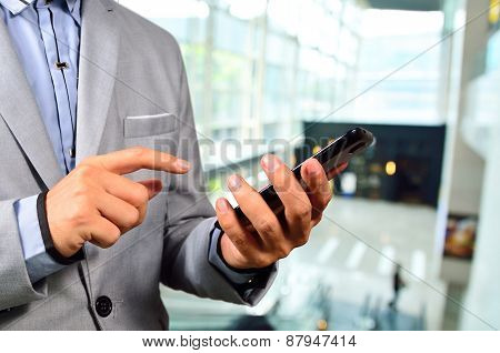 Business Man Using Mobile Cell Phone In The Modern Office Building.