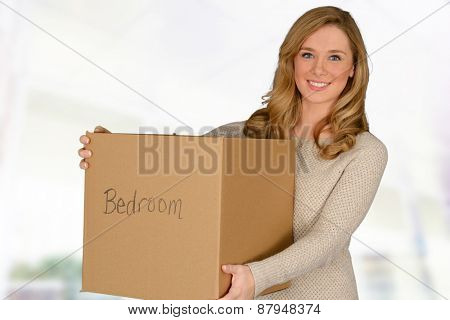 Happy young woman moving in carrying moving box