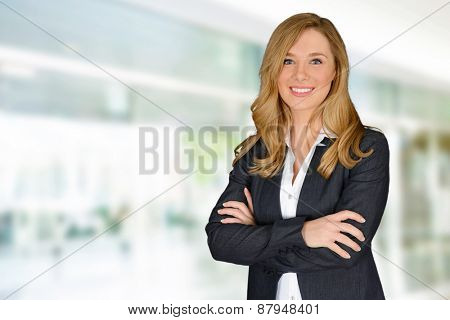 Young successful woman with crossed hands looking at camera
