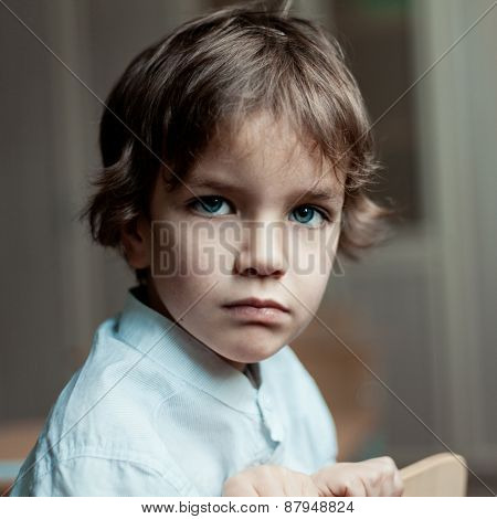 Portrait of serious cute kid boy,  indoor