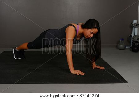 Female doing pushup workout in indoor gym
