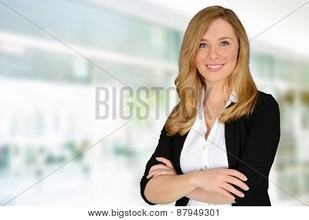 Young blue eyed woman crossing hands and smiling to the camera