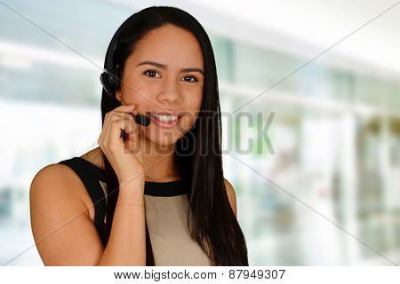 Young happy brunette talking on headset