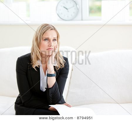 Dejected Businesswoman Holding A Paper And Sitting On A Sofa