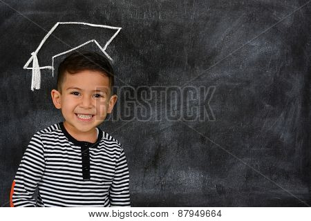 Happy little schoolboy posing in front of black chalkboard