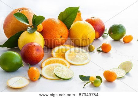 Assorted fresh citrus fruits with leaves