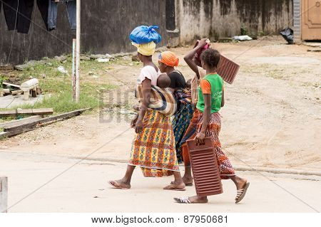 four women walking on the road.