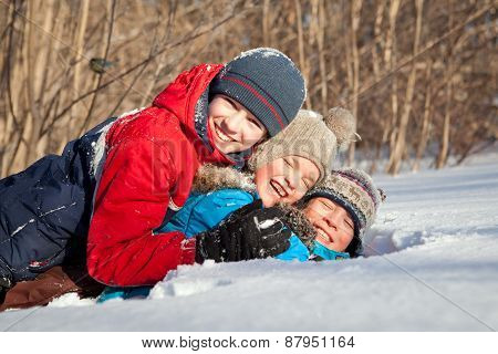 Happy Children In Winterwear Playing In Snowdrift
