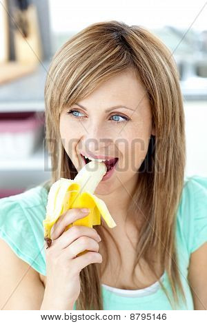 Smiling Young Woman Eating A Banana In The Kitchen